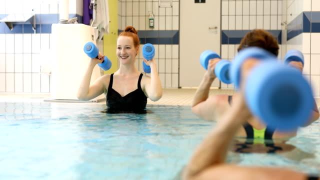 Coach en vrouwen trainen met halters in zwembad
