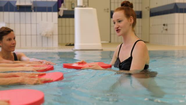 Coach en vrouwen houden van drijvers in zwembad