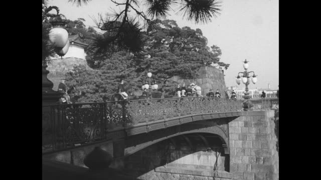 Coach carrying Prince Akihito with mounted escort crosses bridge / angle view of escort following coach crossing bridge / crowd moves along towards...