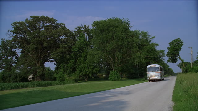 ws pan ts coach driving along country road, moving past welcome sign, texas, usa - welcome schild stock-videos und b-roll-filmmaterial