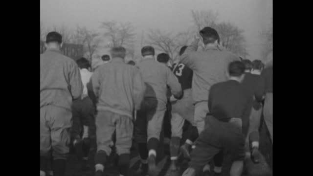 coach elmer layden standing with members of team in sweat clothes for photo opportunity / close shot of layden speaking to camera / team shouting,... - tirare la palla video stock e b–roll