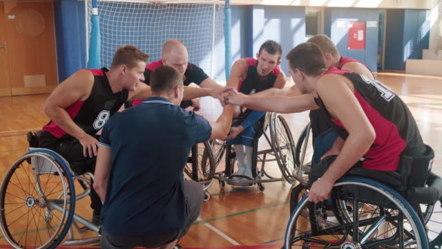 coach encouraging team of wheelchair basketball players - hands clasped stock videos & royalty-free footage