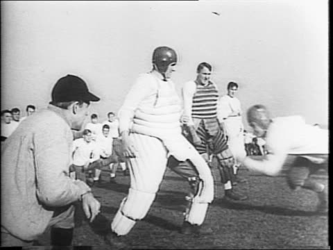 vídeos de stock, filmes e b-roll de coach frank leahy puts big notre dame squad through first spring practice and the boys joins the marines / lines of football players running / notre... - campo de futebol americano