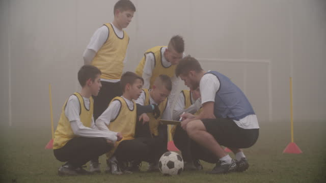 4k: coach giving instruction to his kids soccer team. - football team stock videos & royalty-free footage