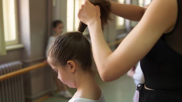 vídeos y material grabado en eventos de stock de entrenador ayudando a la pequeña bailarina a atar su pelo - ballet