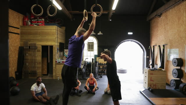 coach helping man with gymnastic rings - gymnastic rings stock videos & royalty-free footage