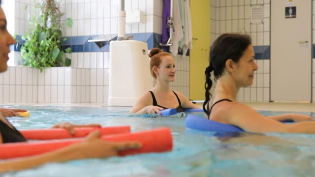 Trainer hält Nudel Schwimmer beim Unterrichten von Frauen