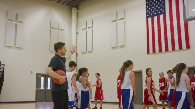 Coach instructing his coed teams during basketball practice