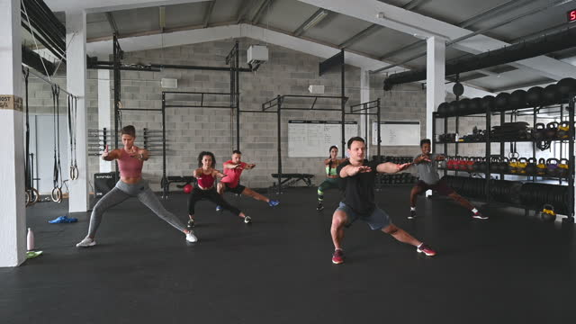 coach leading athletes in side lunge with arms forward - lunge stock videos & royalty-free footage