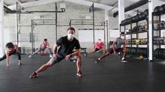 coach leading socially distanced workout in time of covid-19 - lunge stock videos & royalty-free footage