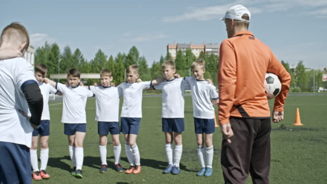 coach motivating kids' soccer team before match - football team stock videos & royalty-free footage