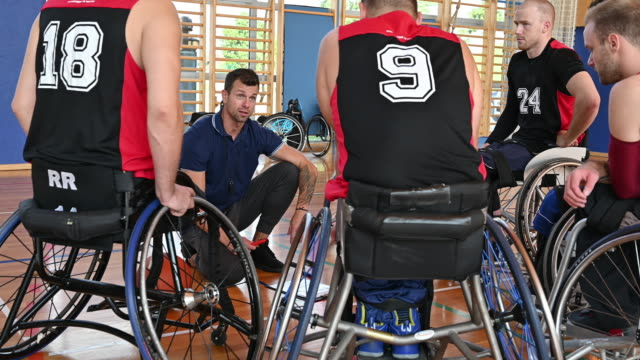 coach motivating wheelchair basketball players in gym - disability stock videos & royalty-free footage