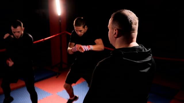 vídeos de stock, filmes e b-roll de técnico em treinamento com pugilistas - posição de combate