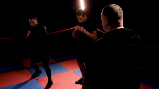 vídeos de stock, filmes e b-roll de técnico em treinamento com pugilistas de chute - posição de combate