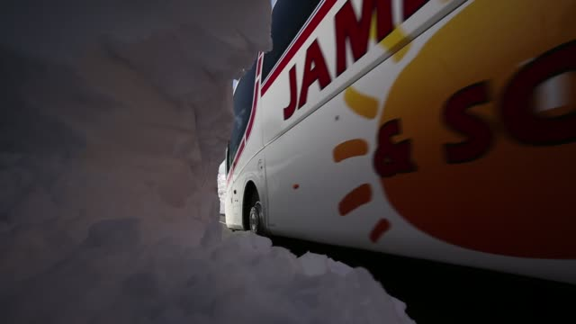 A coach passing large snowdrifts on the A591 road at Thirlmere in the Lake District, UK, following the unseasonal extreme weather events of late march 2013.