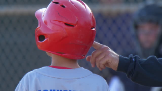 Coach puts his finger in ear of boy playing in a little league baseball game with a red batting helmet. - Slow Motion