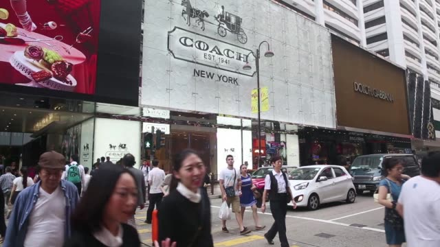 A Coach signage is displayed above the companys store on Canton Road in the Tsim Sha Tsui area of Hong Kong on Tuesday Oct 28 Pedestrians walk past a...