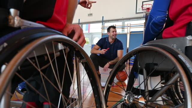 coach strategizing with male wheelchair basketball players - wheelchair basketball stock videos & royalty-free footage