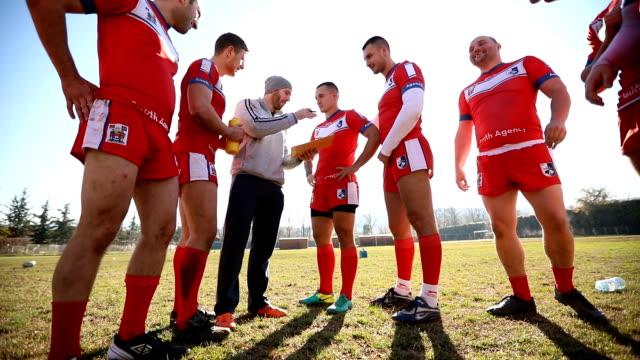 Coach praten met een groep van rugbyspelers