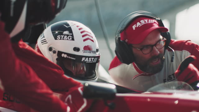 coach talking with driver during sports race - pit stop stock videos & royalty-free footage
