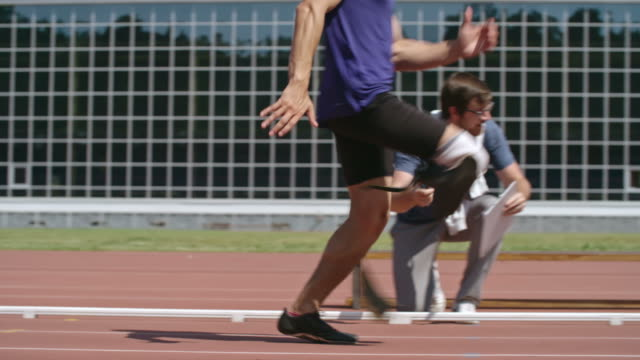 coach timing amputee sprinter at stadium - artificial limb stock videos & royalty-free footage