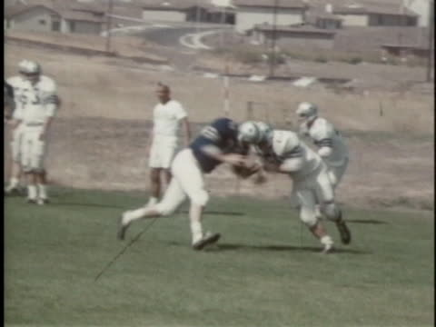 coach tom landry watches quarterback don meredith pass a football to bob hayes. - クオーターバック点の映像素材/bロール