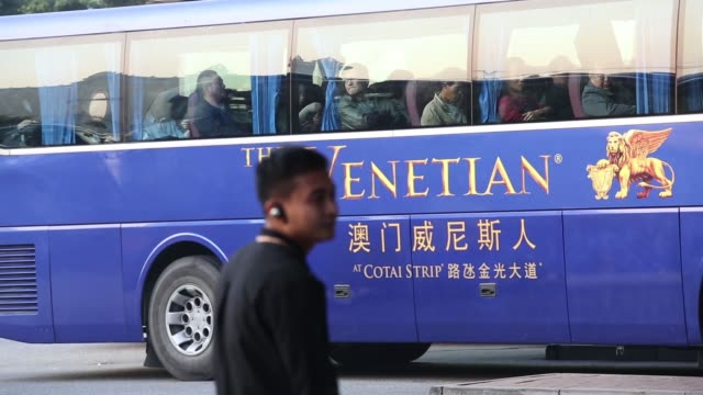 A coach waits at a coach stop outside The Venetian Macao resort and casino operated by Sands China Ltd a unit of Las Vegas Sands Corp A coach loaded...