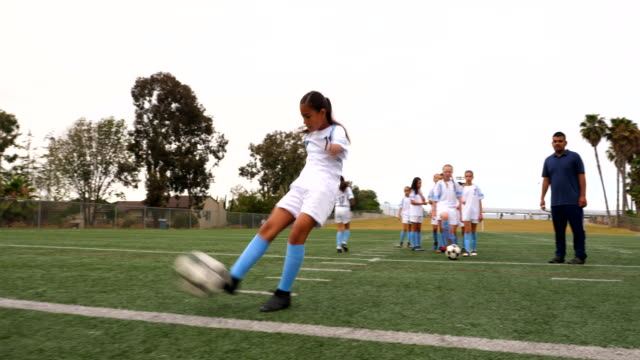 ms coach watching young female soccer player practicing shot before game - strength stock videos & royalty-free footage