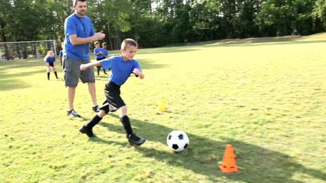 coach with children's soccer team practicing drills - drill stock videos & royalty-free footage