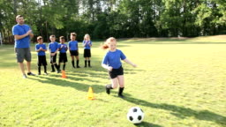 Coach with children's soccer team practicing drills