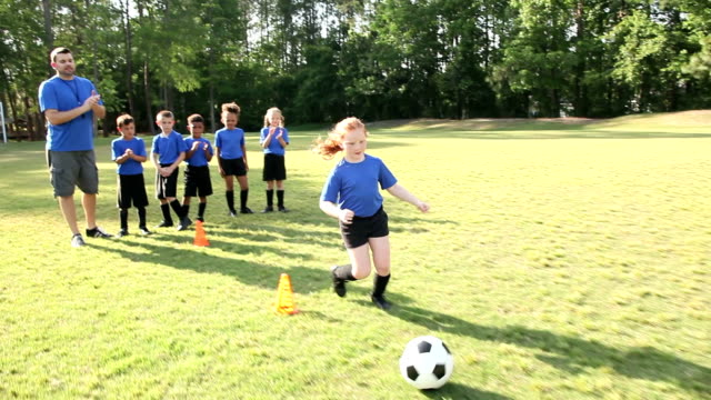 coach with children's soccer team practicing drills - calcio sport video stock e b–roll