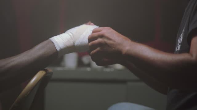 A coach wraps a boxer's hands.