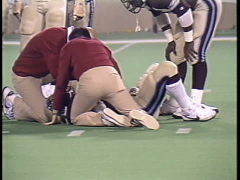 1984 MS Coaches checking on Michigan Panthers' Ken Lacy after Lacy is injured in tackle during game against Pittsburgh Maulers/ Pontiac, Michigan