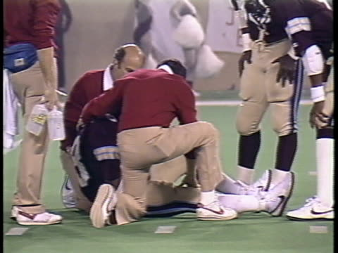 1984 MS Coaches checking on Michigan Panthers' Ken Lacy after Lacy is injured in tackle during game against Pittsburgh Maulers/ Lacy getting up and holding arm/ Pontiac, Michigan