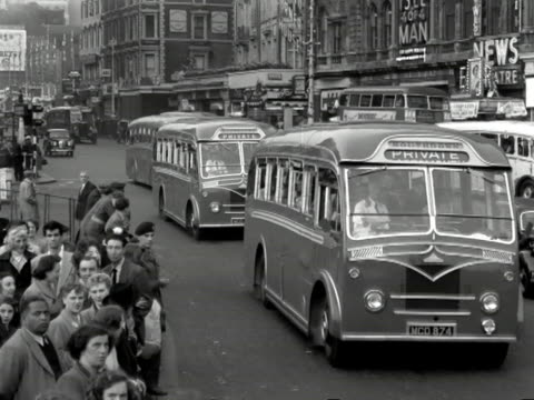 Coaches of tourists move along a busy London road during the Coronation celebrations 1953