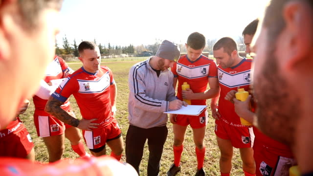 coaching rugby players on the field - allenatore video stock e b–roll