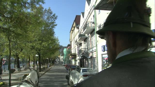 coachman drives horse-drawn carriage round streets of bad ischl, austria - オーストリア点の映像素材/bロール