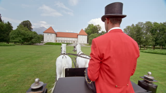 slo mo coachman driving the carriage towards castle - top hat stock videos & royalty-free footage