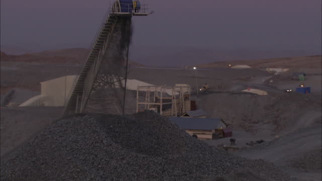 a coal crusher empties coal below a coal miner on a platform in south africa. - miner stock videos & royalty-free footage