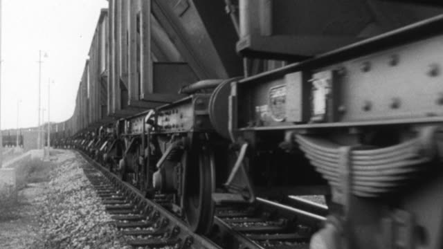 1965 montage coal field with smokestacks in background, trains speeding on track carrying products with dr. beeching narrating use of railway to transport products / united kingdom - narrating stock videos & royalty-free footage