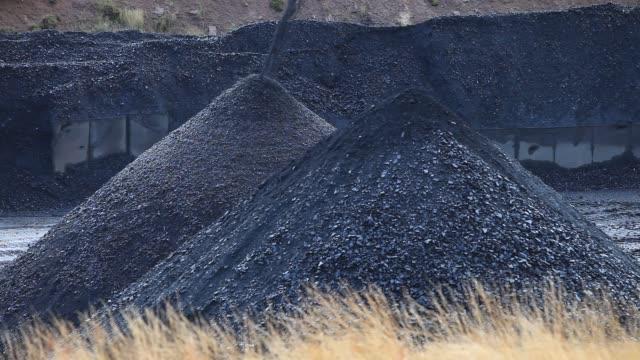 coal from the gentaggart open cast coal mine that has been taken by conveyor belt to the roadside for onward transport, lanarkshire, scotland, uk. - roadside stock videos & royalty-free footage