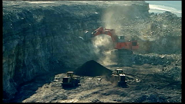 coal industry concerns about impact on jobs of curbs on carbon emissions; usa: west virginia: ext pile of coal truck tipping load of coal onto back... - kohlengrube stock-videos und b-roll-filmmaterial