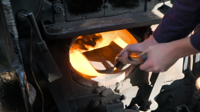 coal is scooped and loaded into a hot furnace - furnace stock videos & royalty-free footage