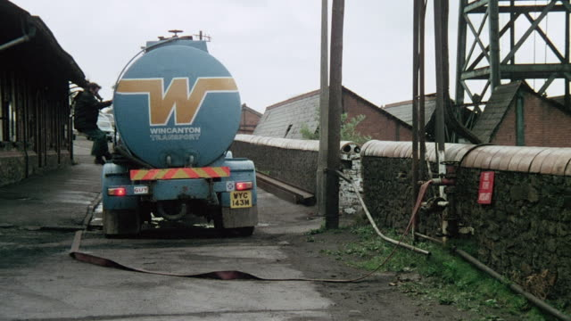 MONTAGE Coal mine buildings, employee descending from truck and walking to turn on tanker pump hose, water pipes pumping and rushing water into river / Wales, United Kingdom