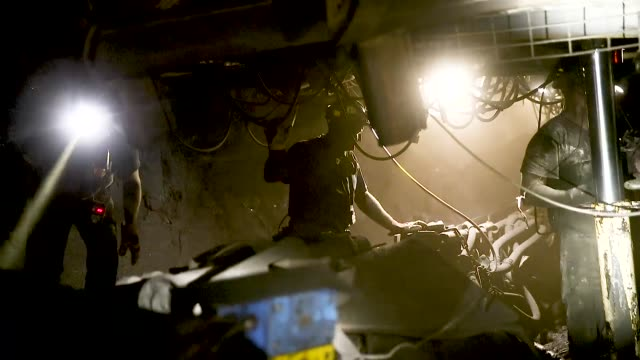 a coal miner and his colleagues shift equipment in the shaft where a machine is grinding coal from a wall approximately 1000 meters below the surface... - mine shaft stock videos and b-roll footage