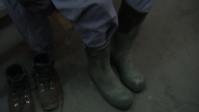 vidéos et rushes de a coal miner puts on rubber boots. - mineur de charbon