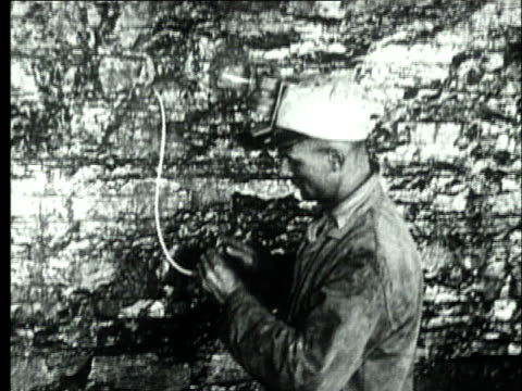 1927 B/W MS Coal miner using flame from oil headlamp to ignite fuse on dynamite placed in coal face/ Pennsylvania, USA