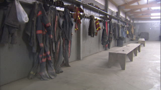 Coal miner's dusty clothing jumpsuits jackets w/ reflecting strips other clothing hanging on pegs below shelving in large open room w/ benches
