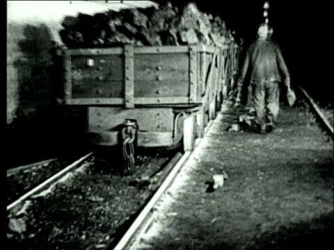 1927 b/w montage ws coal miners signalling train of mine carts filled with bituminous coal in underground mine/ pennsylvania, usa - minatore video stock e b–roll