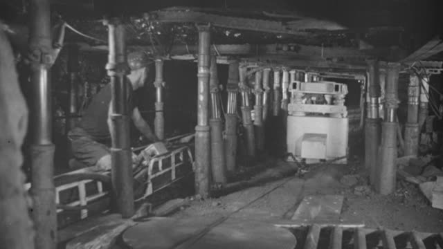 1969 MONTAGE Coal mining machines in action in a coal mine and technicians observing new coal mining equipment in a lab setting / United Kingdom